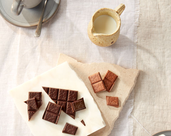 Pieces of chocolate with a jug of milk.