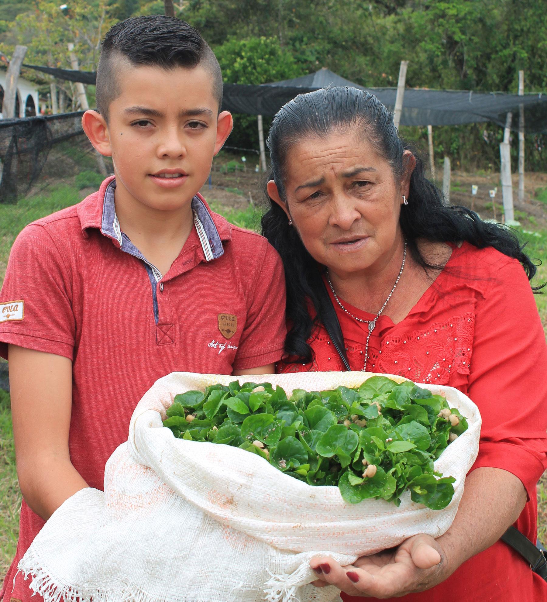 Jorge en grootmoeder houden koffieplanten vast