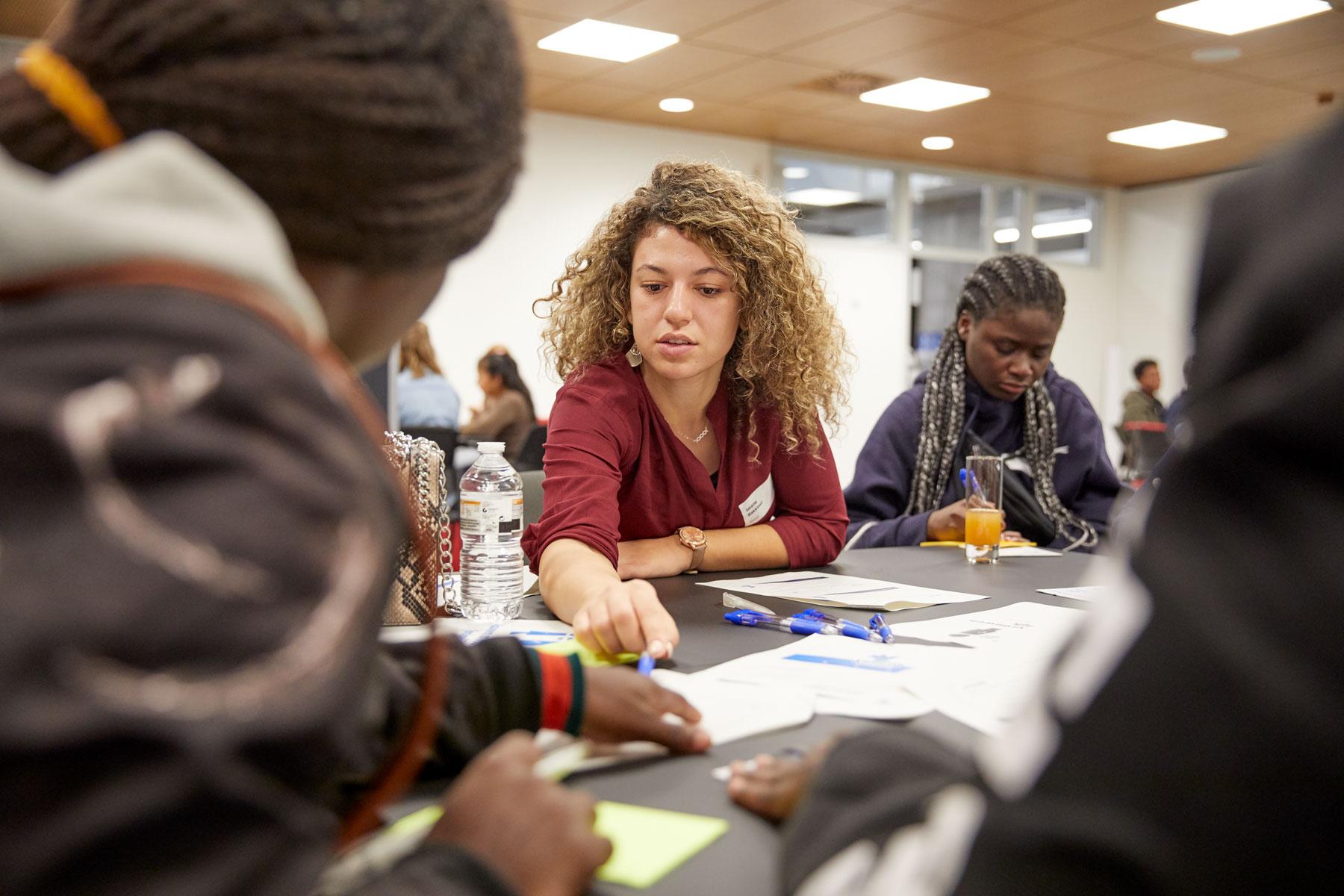 Imane discute avec d'autres jeunes à propos des inégalités entre les hommes et les femmes